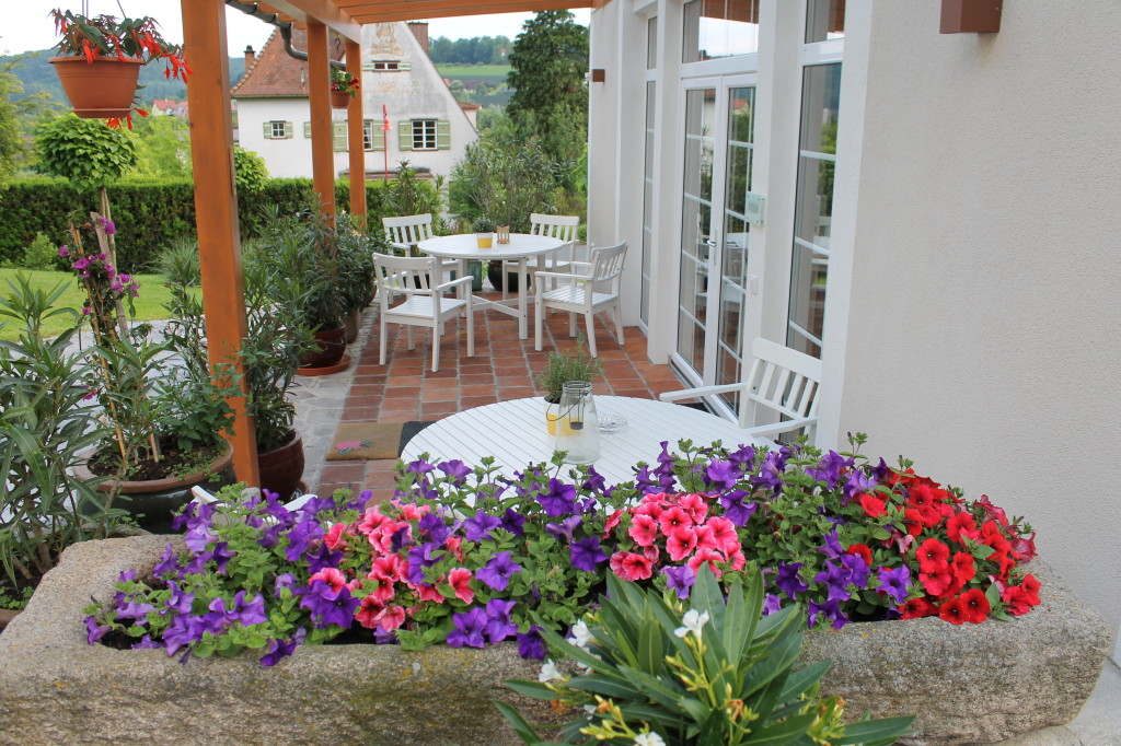 Unser Häuserl von draussen ist umgeben von Blumen und zwei feinen Sitzgarnituren.